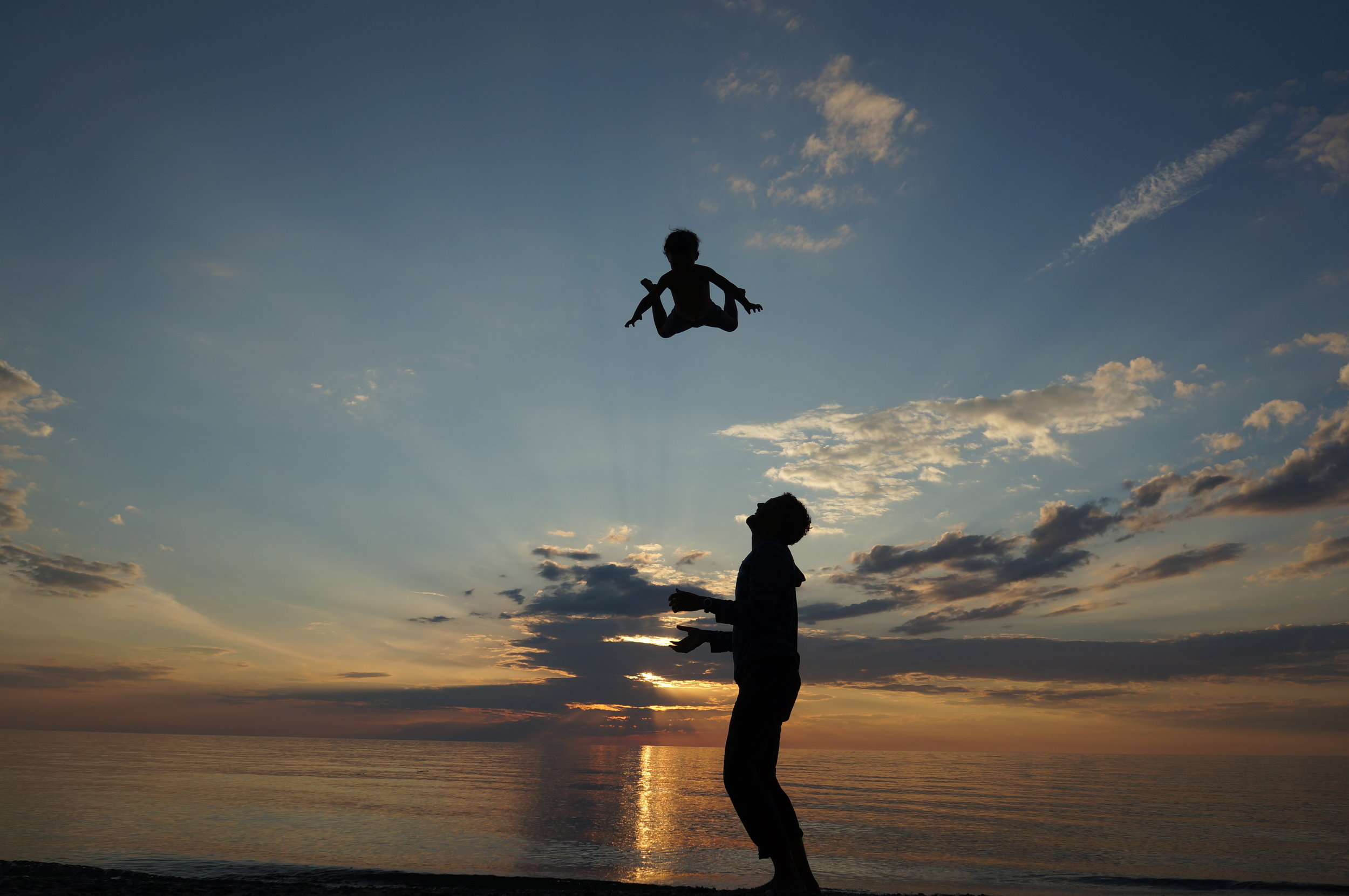 Toddler tossing at sunset.