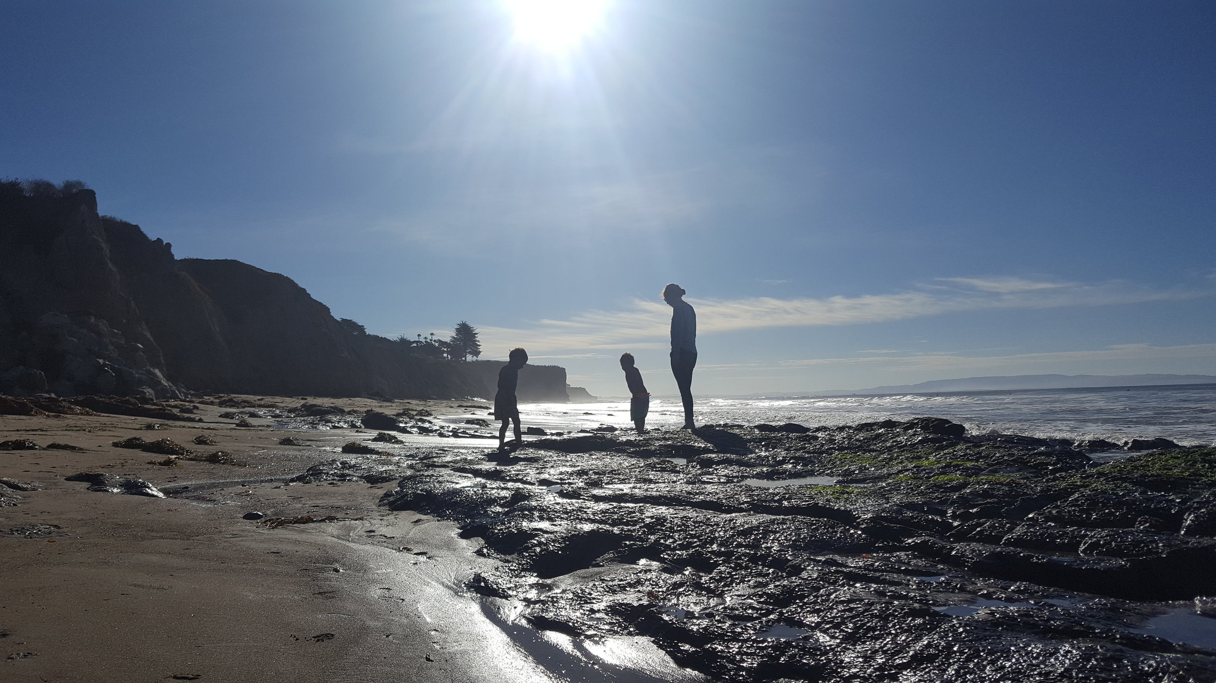 Lydia and the boys looking for sea life at Shell Beach .