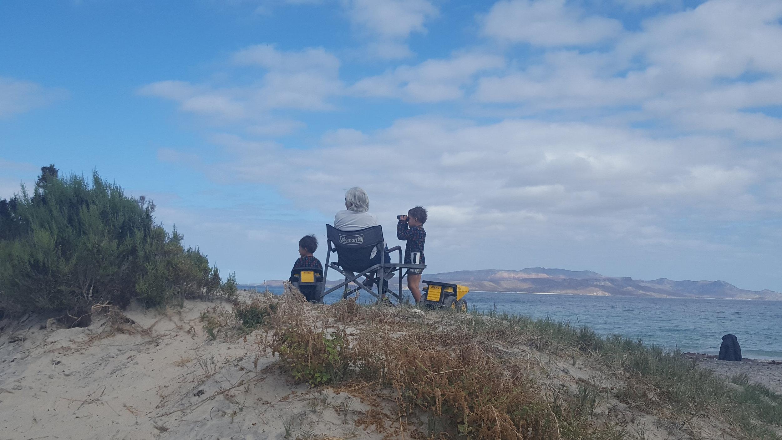Bennett using his truck as a chair, while Reid borrows Fern's binoculars