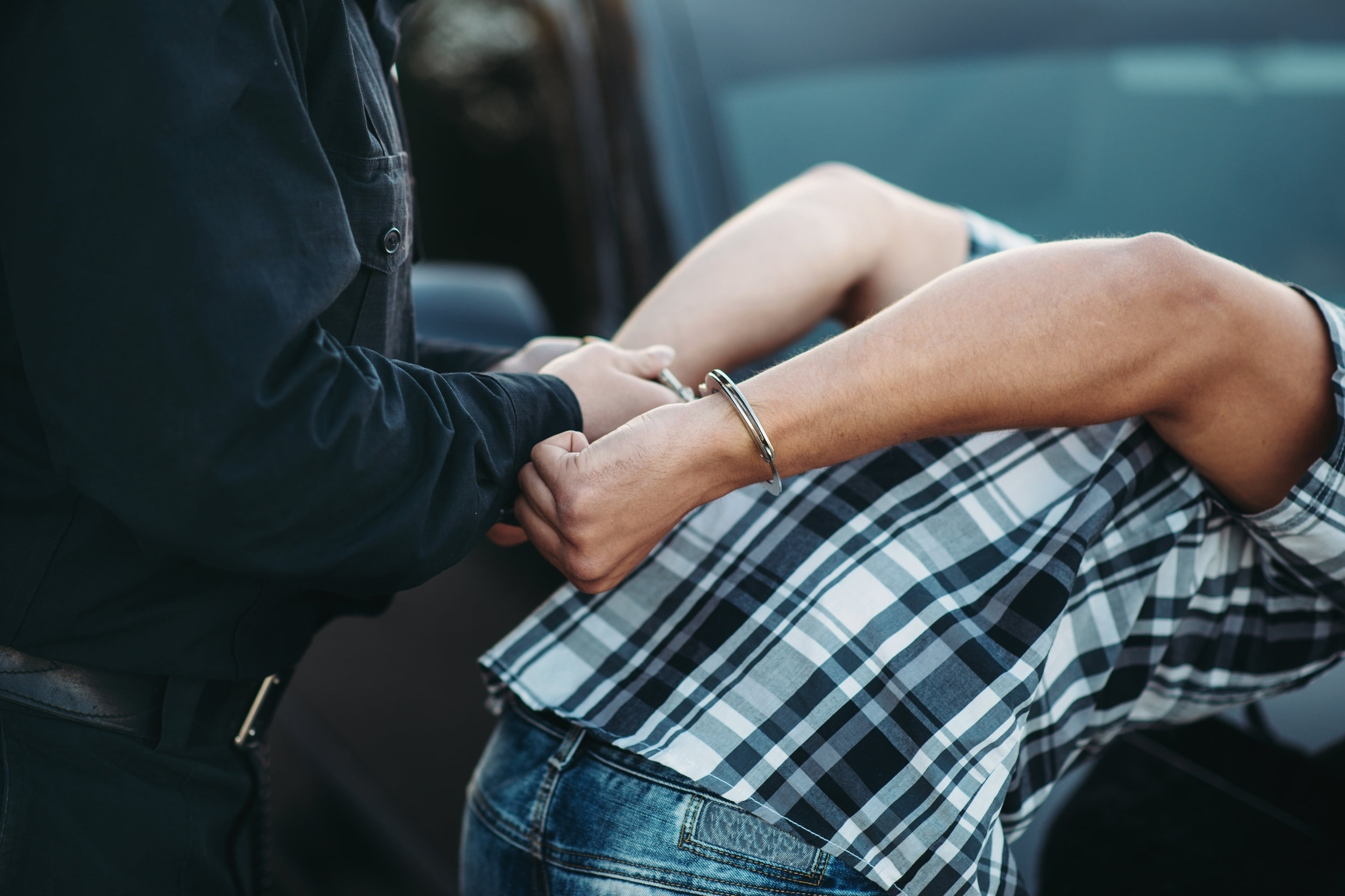 police-officer-puts-handcuffs-on-a-car-thief-5MPUJ9G.jpg