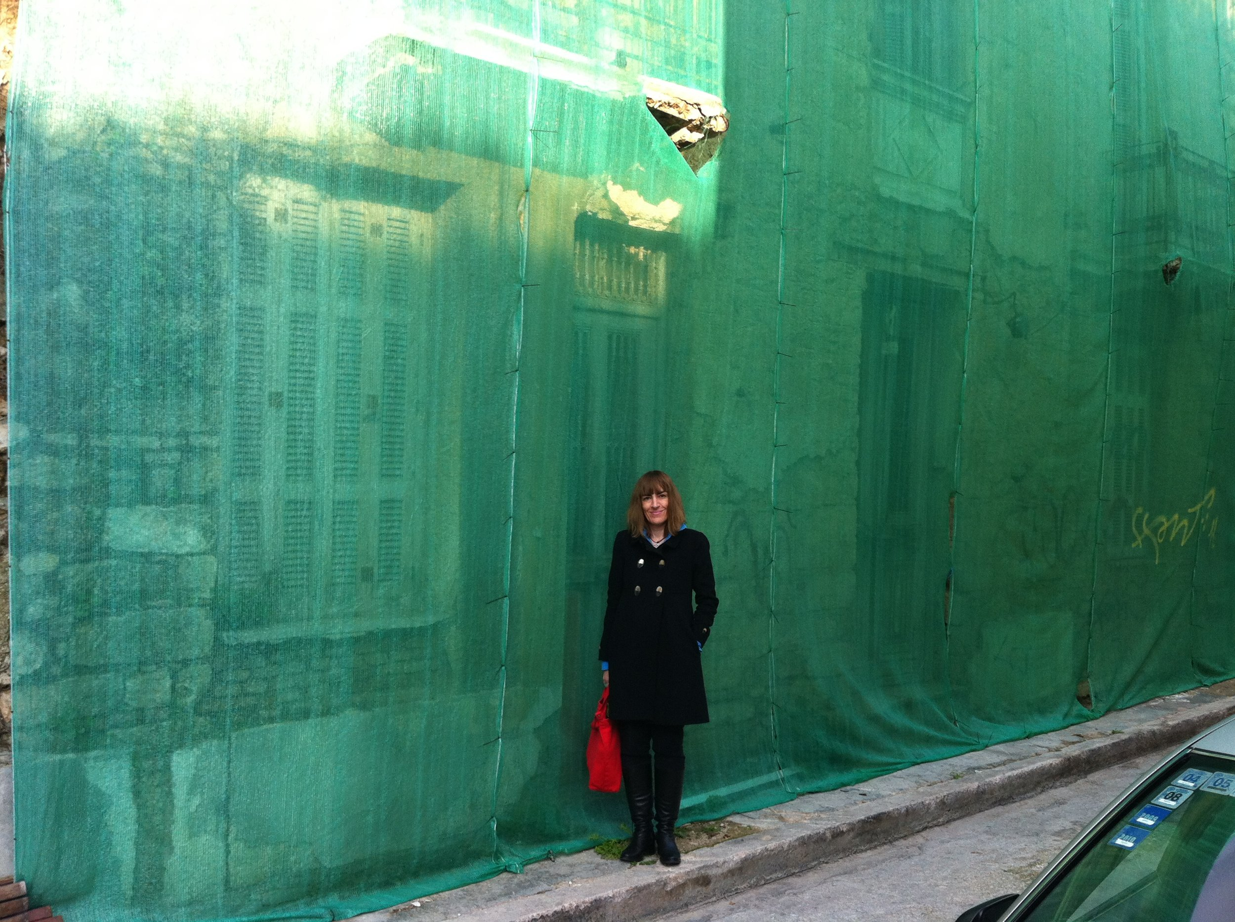 Ioanna Theocharopoulou standing under a building facade under renovation in Athens, 2012. Courtesy of the author.