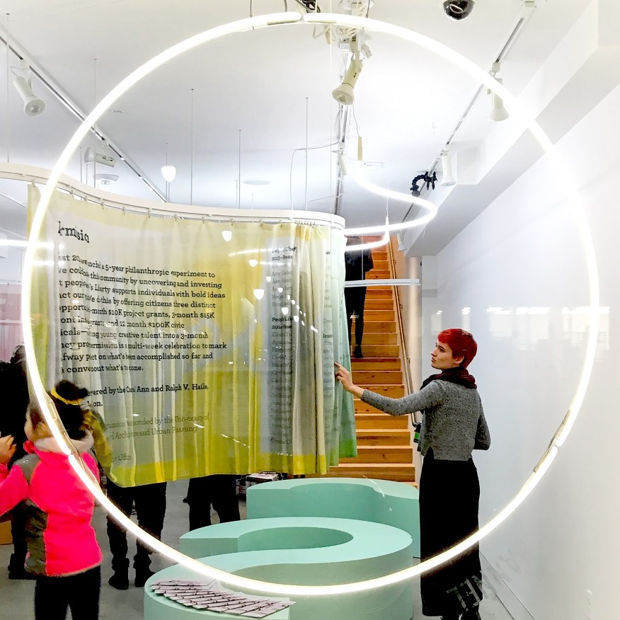 "The duo utilized elements typical of the theater—lighting, curtains, and rows of seating—for the Inter-Mission storefront exhibit design. Visitors were invited to ""scroll"" through custom-printed curtains that doubled the available display space. Courtesy Outpost Office"