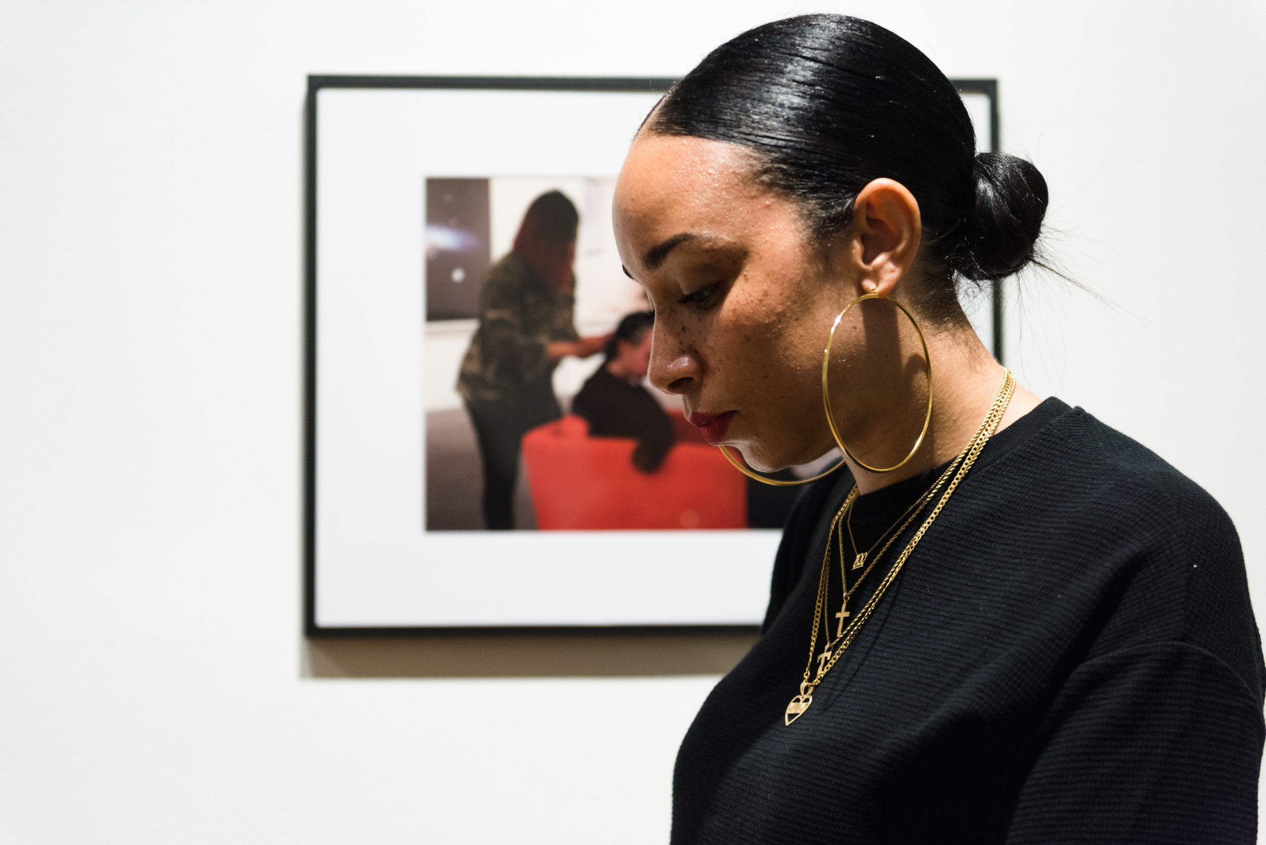 Fay at the Associated Artists of Pittsburgh Annual New Members Exhibition where she presented on her performance piece,  Flow State . The documentation titled,  Hair Braiding at the CMoA,  of the performance is pictured in the background and on view at the exhibition. Courtesy Chris Uhren.