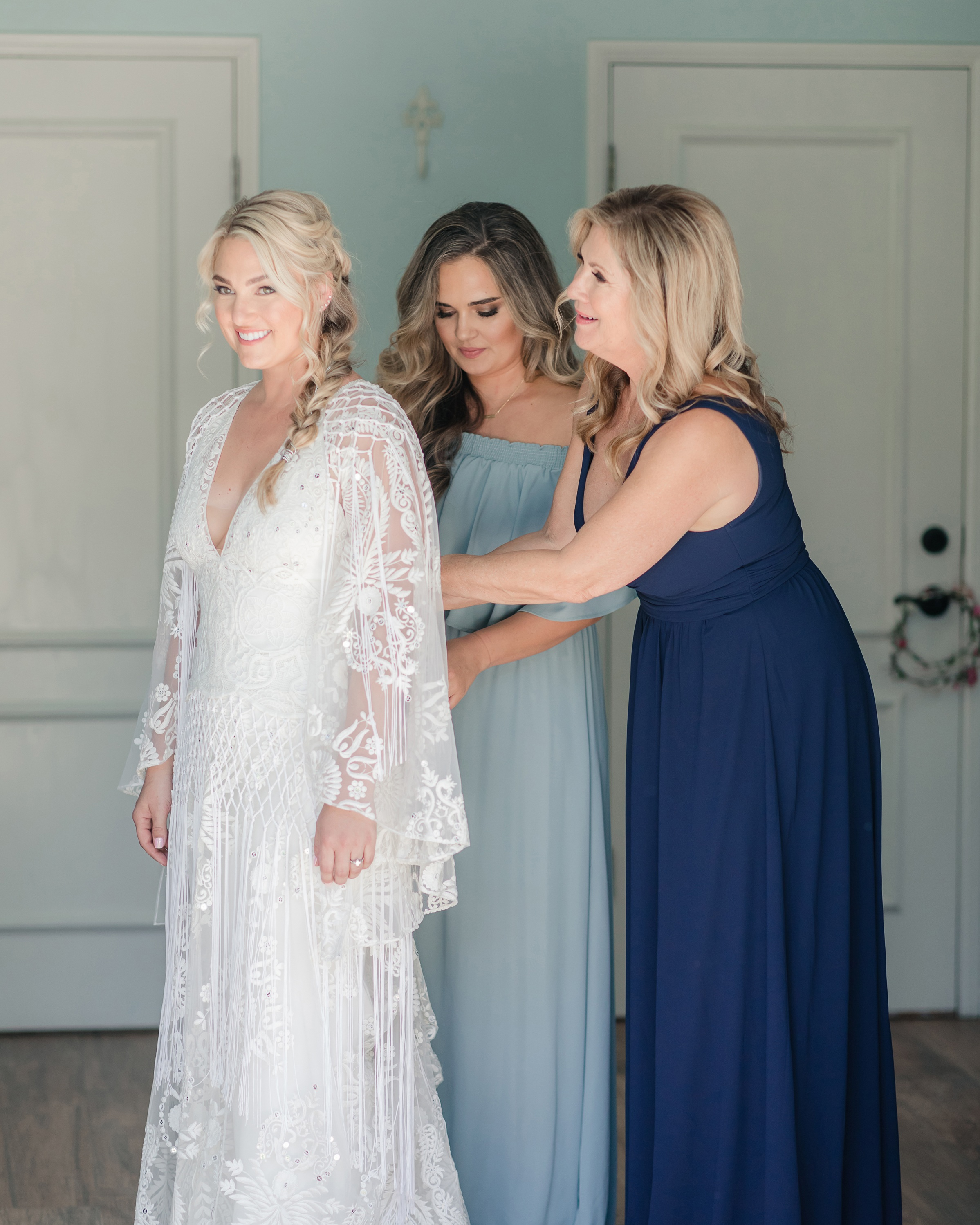 Mother of the bride and matron of honor helping this Malibu bride into her dress
