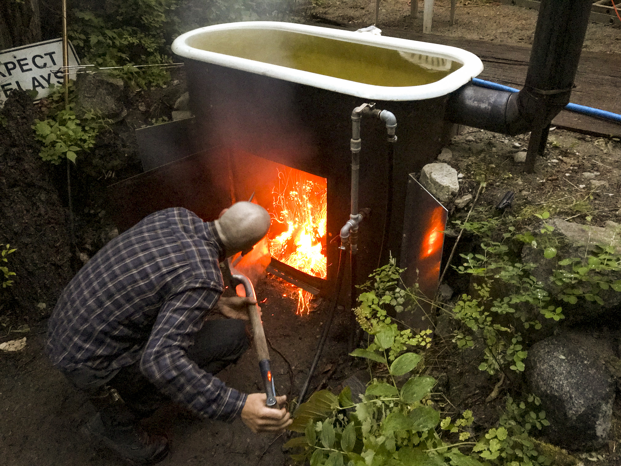 Jeff Radomsky heating up the wood-fired hot tub in advance of a soak. The tub, which is fed by a siphon line from the creek, provides hot water for the outdoor shower.
