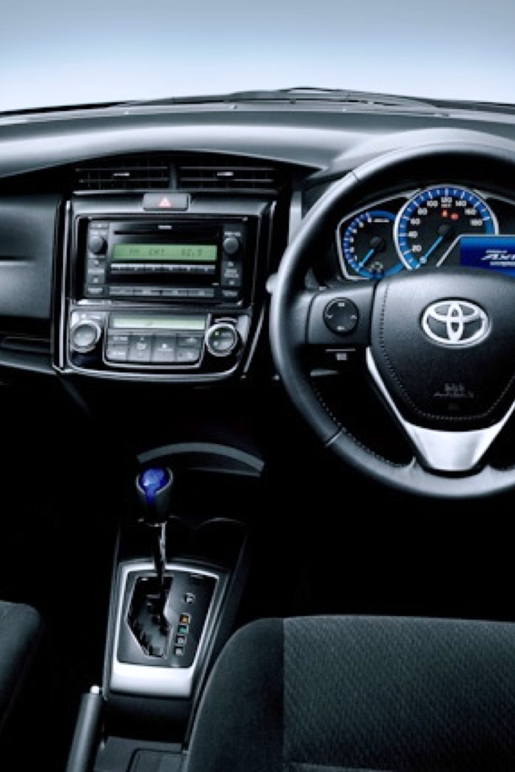 Car interior of a Toyota. Image shows steering wheel and gear stick