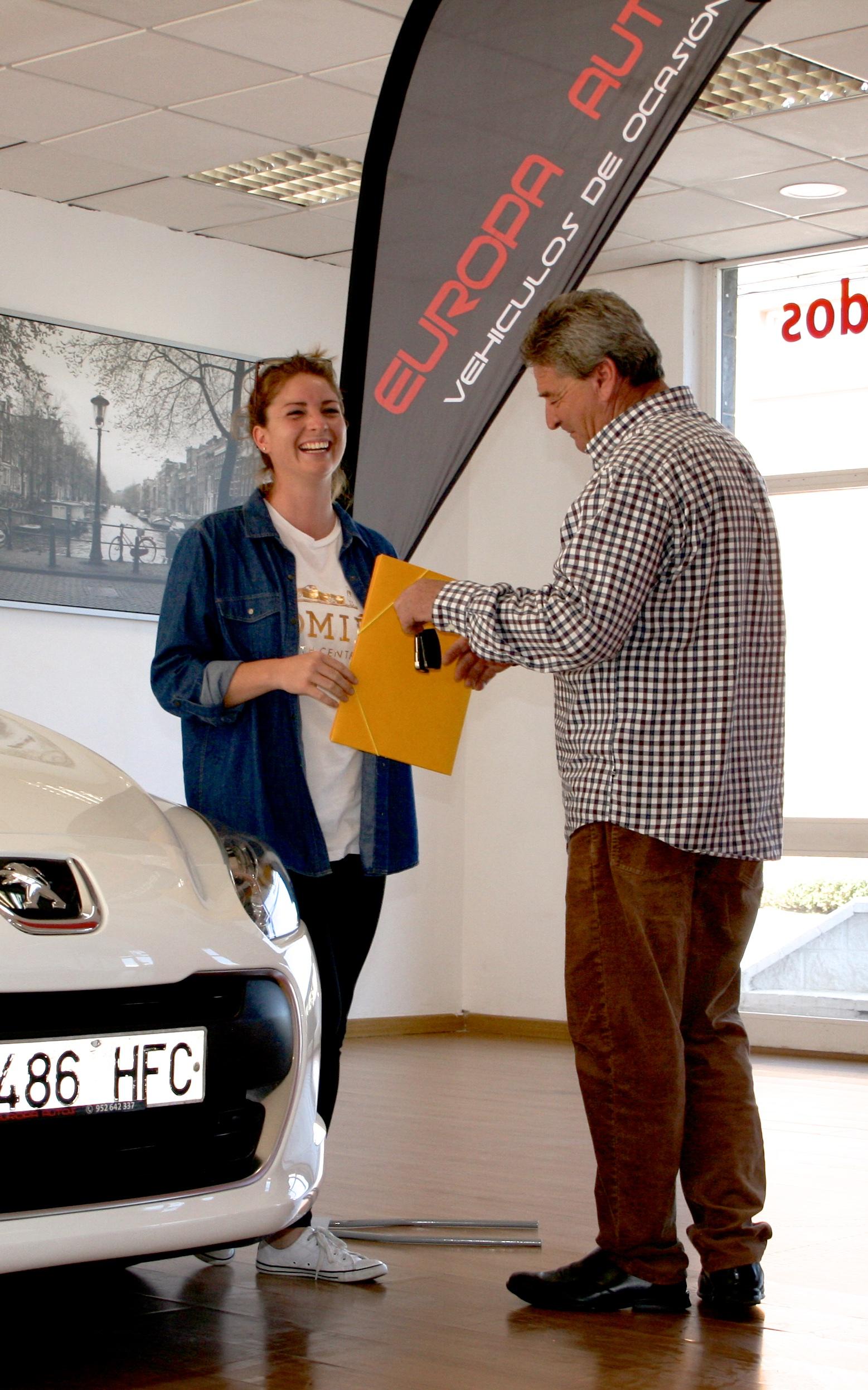 Mujer comprando un Peugeot blanco en el concesionario de Europa Autos en Malaga.