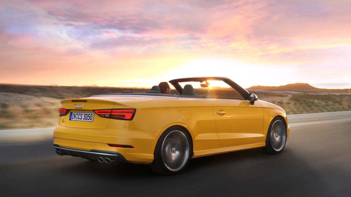 Audi descapotable amarillo conduciendo con velocidad al atardecer