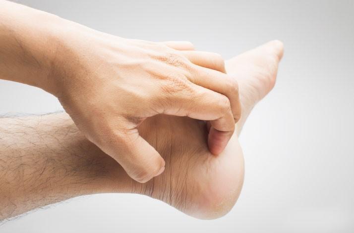 man scratching foot