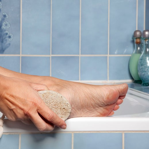 woman scrubbing her heels with a pumice