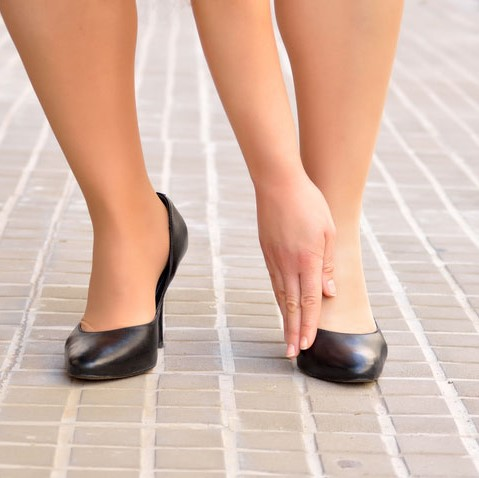 woman in heels touching her bunion
