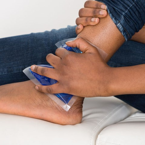 person putting an ice pack to their ankle