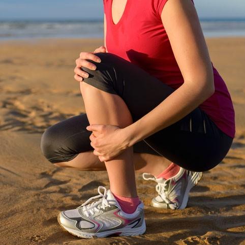woman running on the beach with shin splints