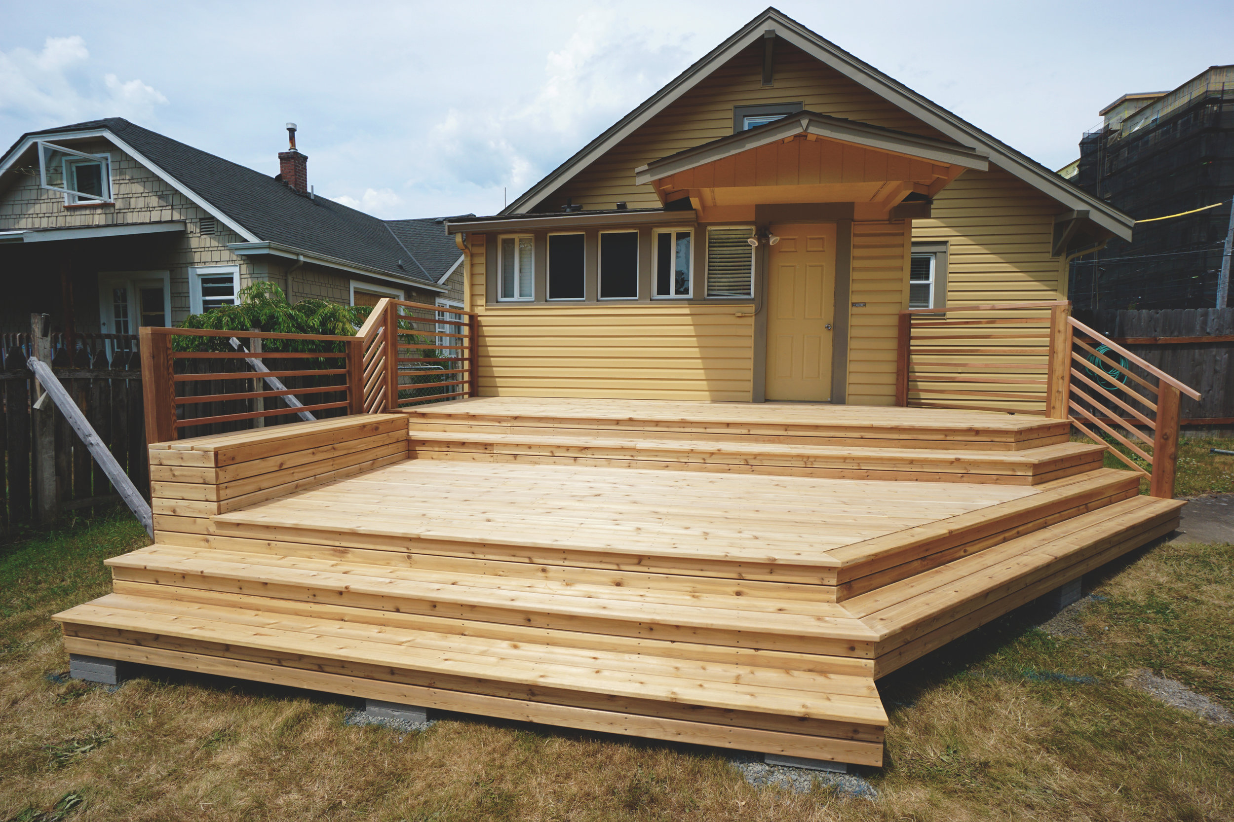 "Modern deck with built-in seating  (Deck composed of 6"" & 4"" decking. Built with all tight knot cedar lumber.)"