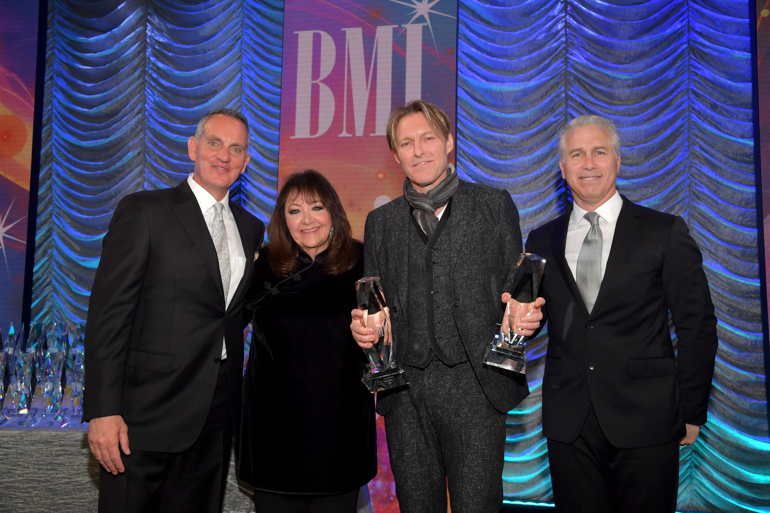 BEVERLY HILLS, CALIFORNIA - MAY 15: (L-R) BMI President & Chief Executive Officer Mike O'Neill, BMI Creative - Film, TV & Visual Media VP Doreen Ringer-Ross, Tyler Bates, and BMI Executive Vice President of Creative & Licensing Mike Steinberg pose onstage during the 35th annual BMI Film, TV & Visual Media Awards on May 15, 2019 in Beverly Hills, California. (Photo by Lester Cohen/Getty Images for BMI)