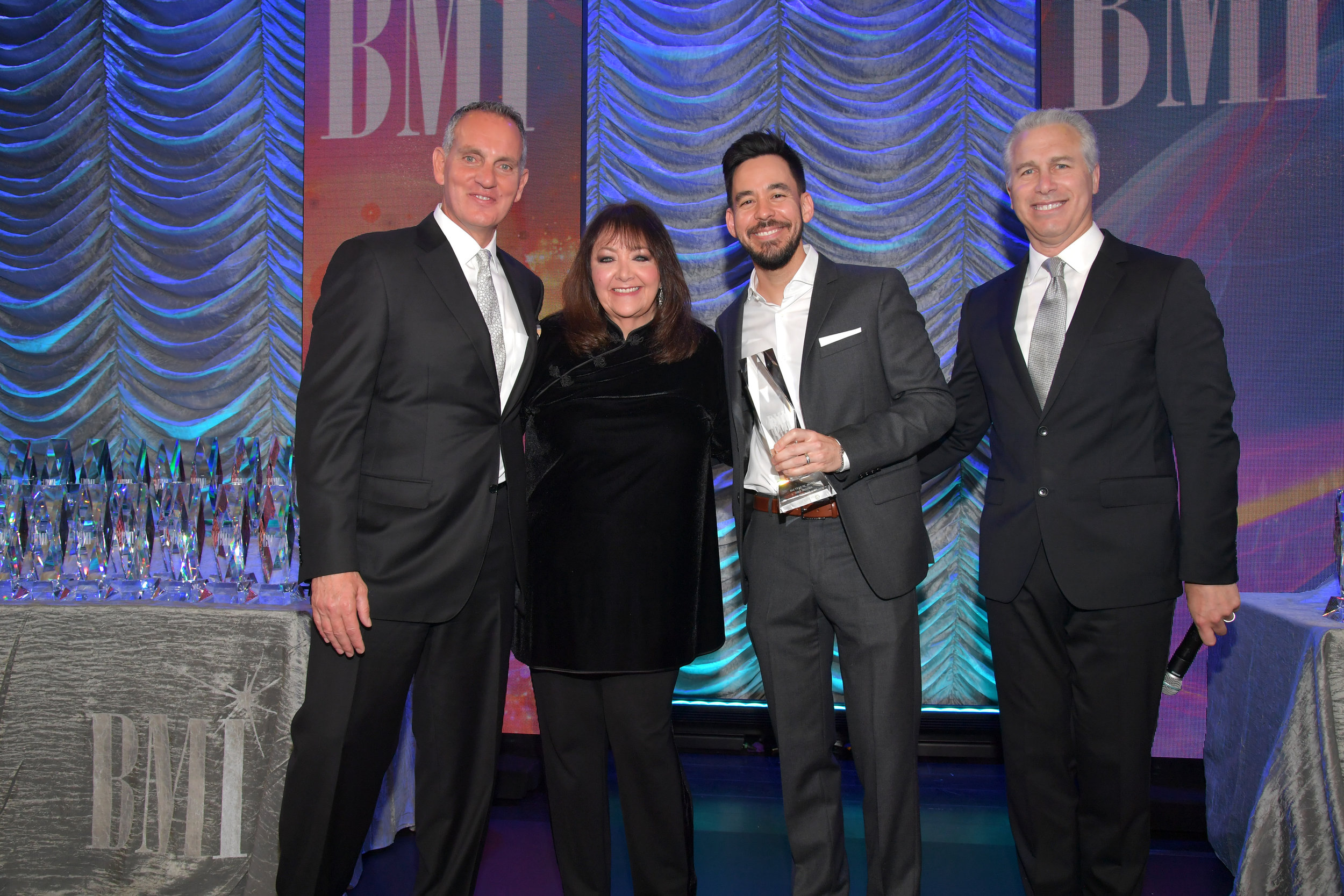 BEVERLY HILLS, CALIFORNIA - MAY 15: (L-R) BMI President & Chief Executive Officer Mike O'Neill, Mike Shinoda, BMI Creative - Film, TV & Visual Media VP Doreen Ringer-Ross, and BMI Executive Vice President of Creative & Licensing Mike Steinberg pose onstage during the 35th annual BMI Film, TV & Visual Media Awards on May 15, 2019 in Beverly Hills, California. (Photo by Lester Cohen/Getty Images for BMI)
