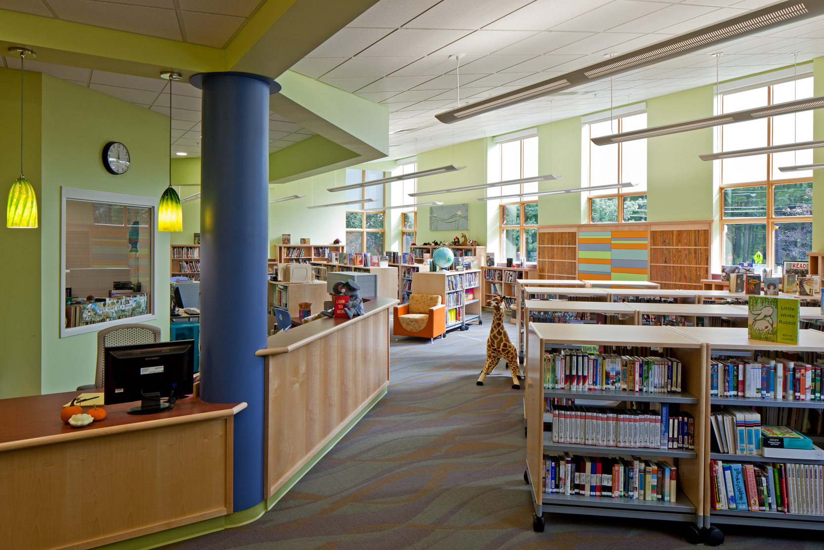 The library contains a built-in story and presentation area, a small classroom, and a variety of seating.