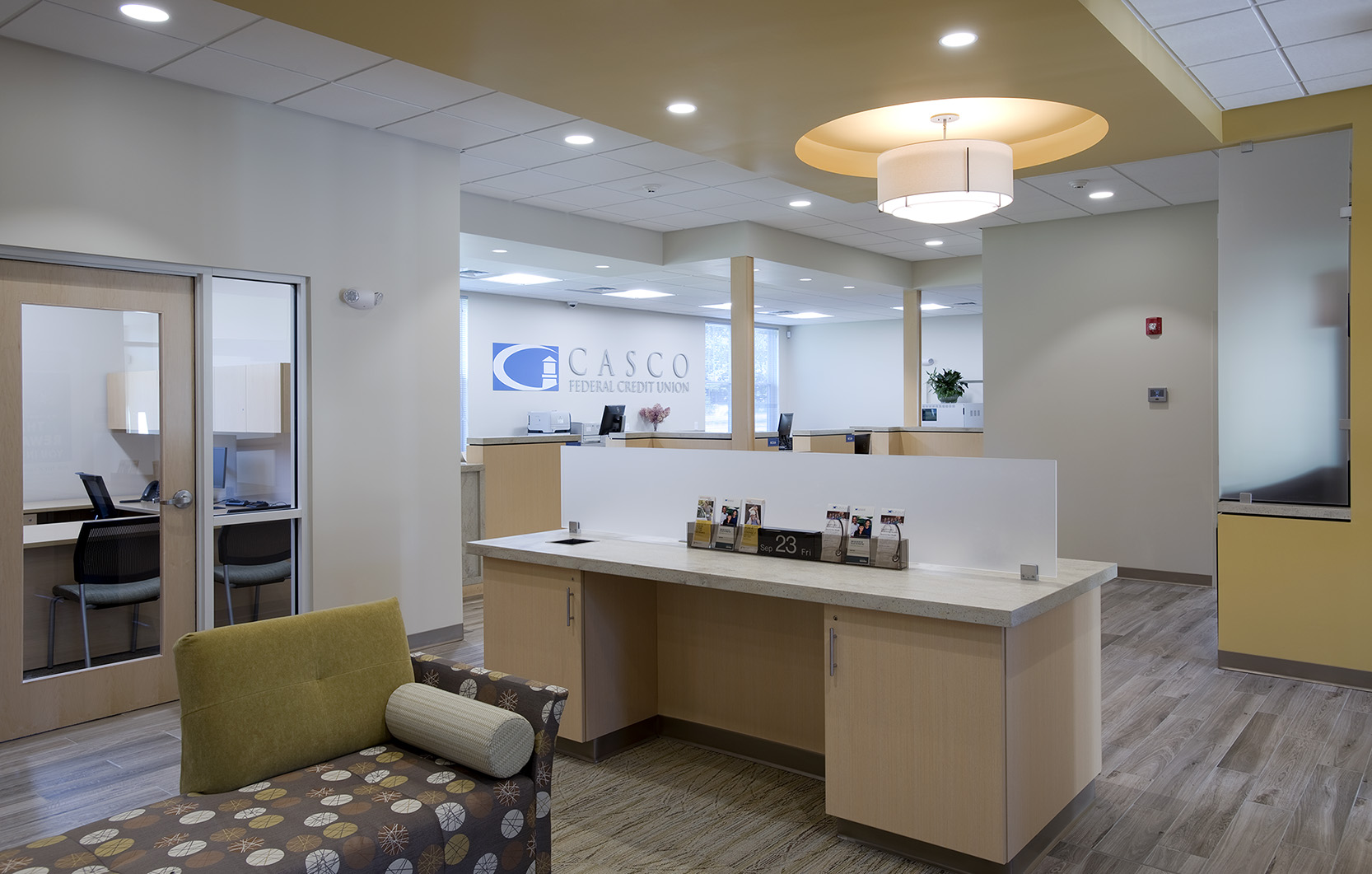 Glass-walled offices lining the perimeter of the branch transmit plenty of natural light to the center of the space.