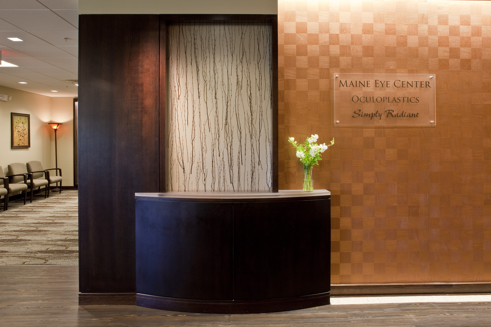 The entry to the facility sets a tone with high-end finishes and a hospitality aesthetic. To the left is Oculoplastics; to the right, Simply Radiant.