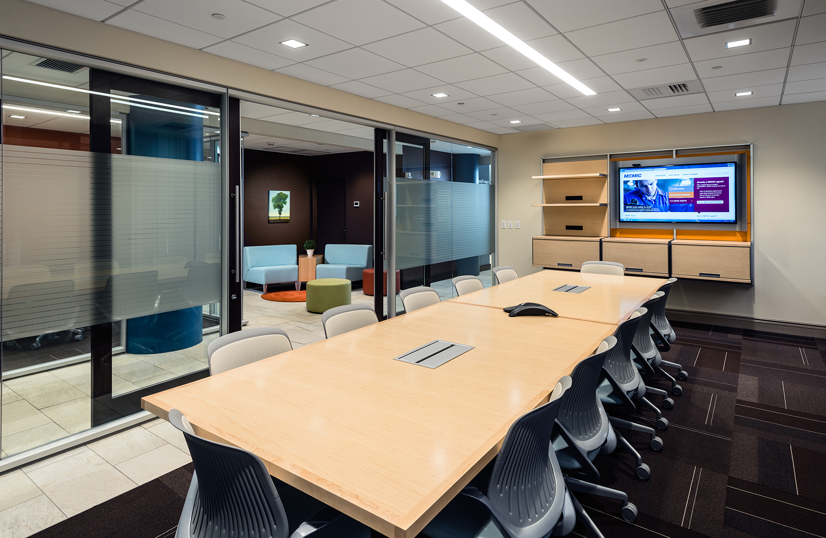 Glass walls open the first-floor conference room to borrowed light, and a corner seating area encourages spontaneous conversations.