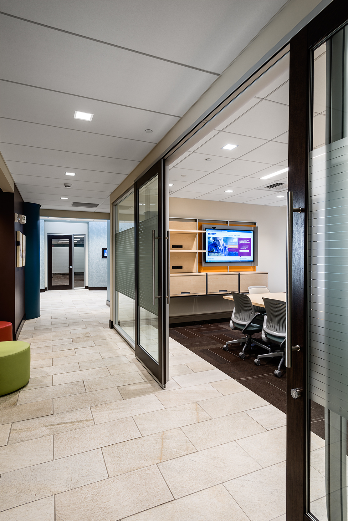 Glass partitions and a sliding door turn an awkward, narrow space into a conference hub, with a small seating area to the left.