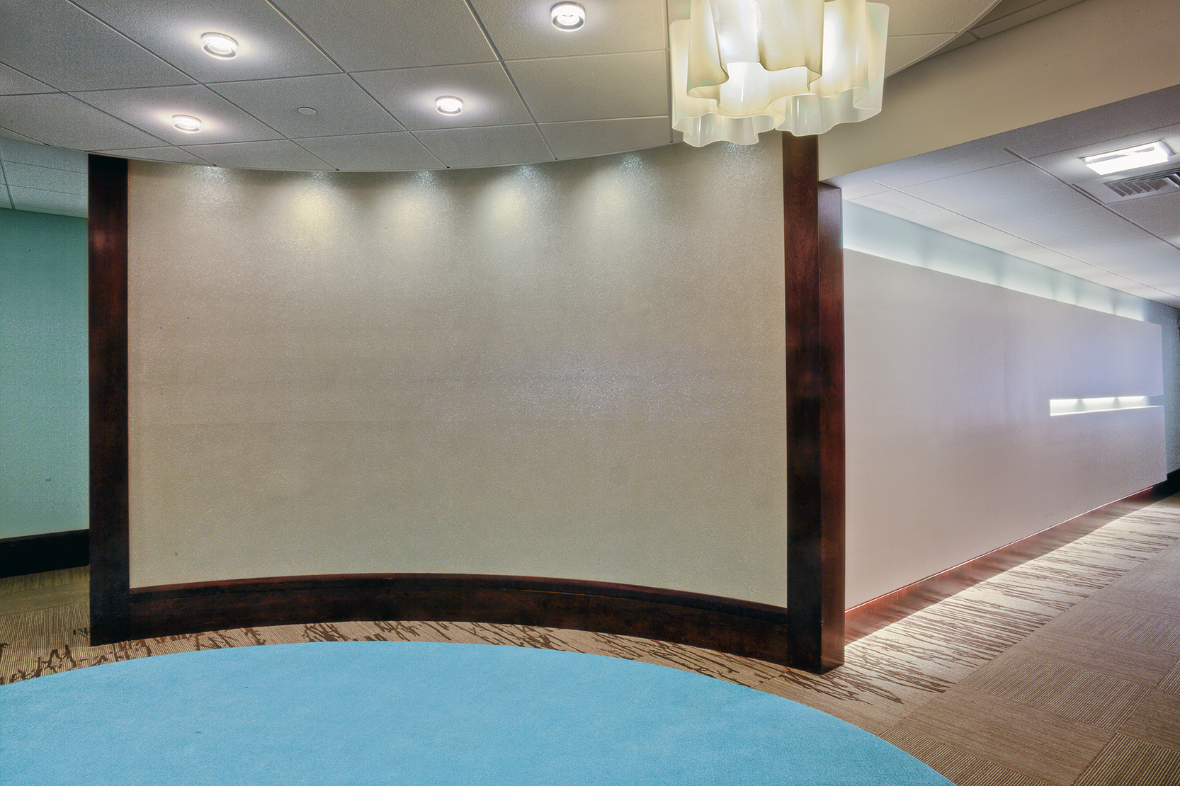 The sparkling curved wall adds the illusion of space at the end of the long hall.