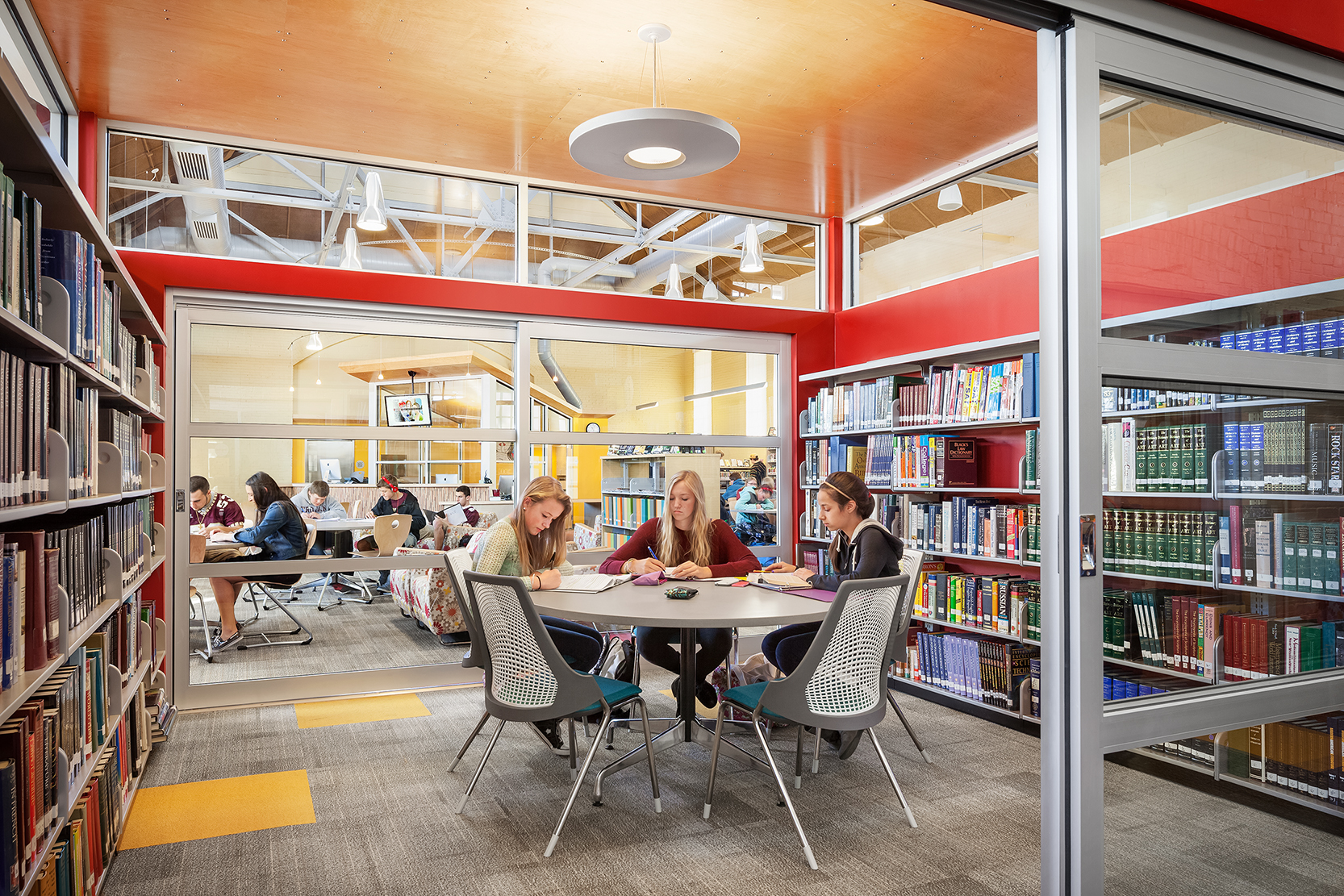Freestanding study and conference rooms in the learning commons delineate quiet research spaces from noisier collaboration areas.