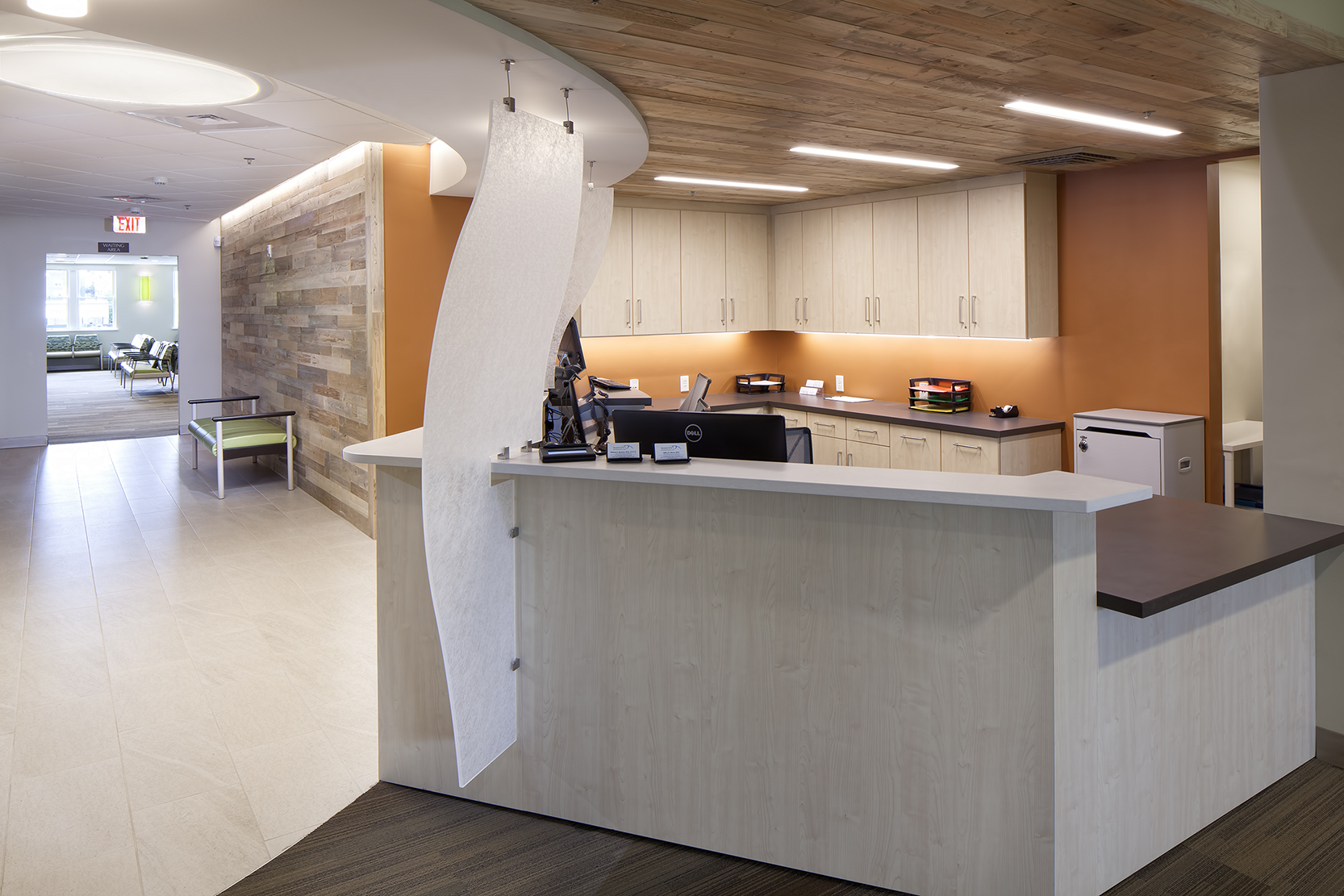 Warm finishes for the check in desk for Lasik and exam patients include reclaimed Maine timber on walls and ceilings and a quartzite visual tile.