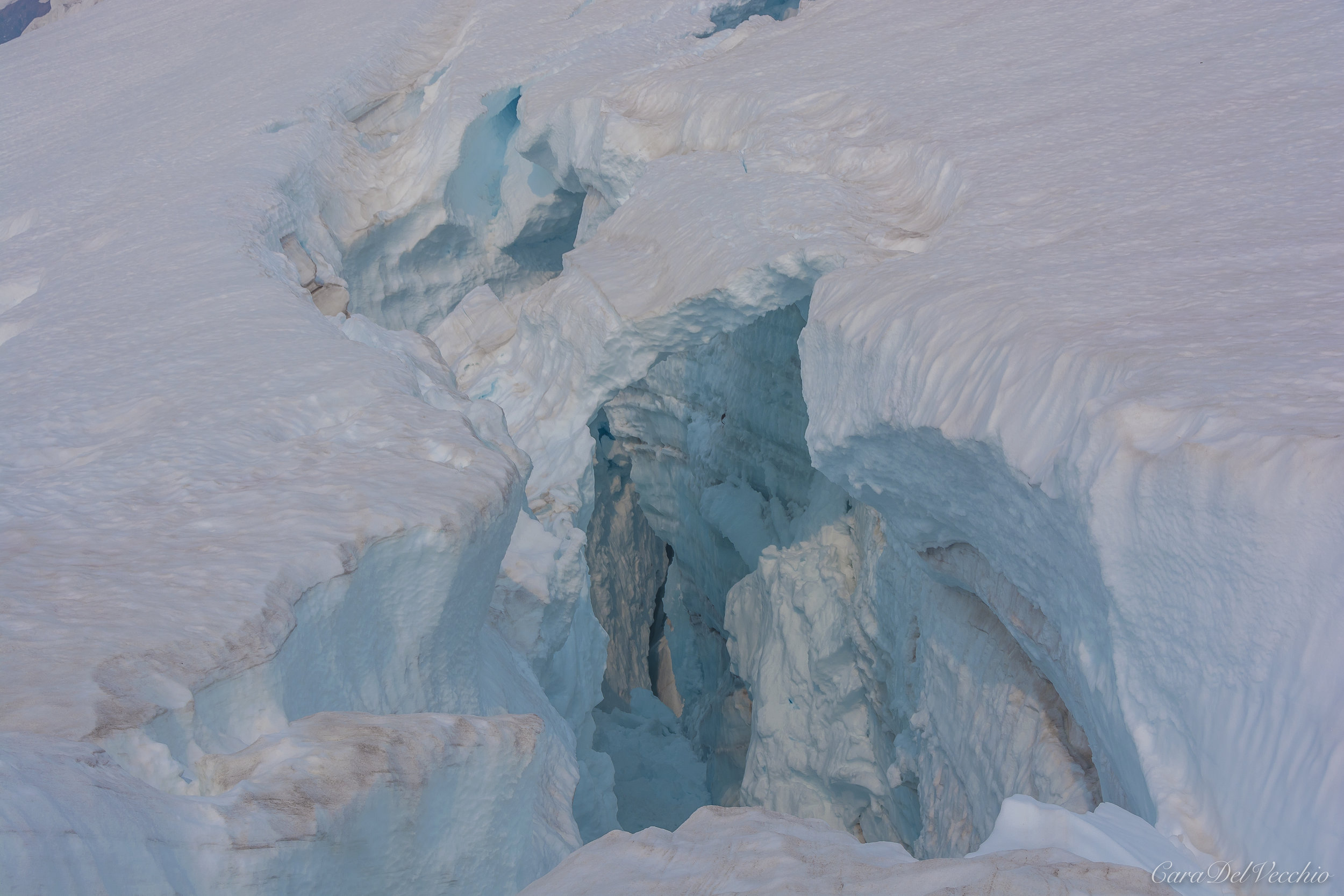 Looking into a deep crevasse; note collapsing ice bridge.