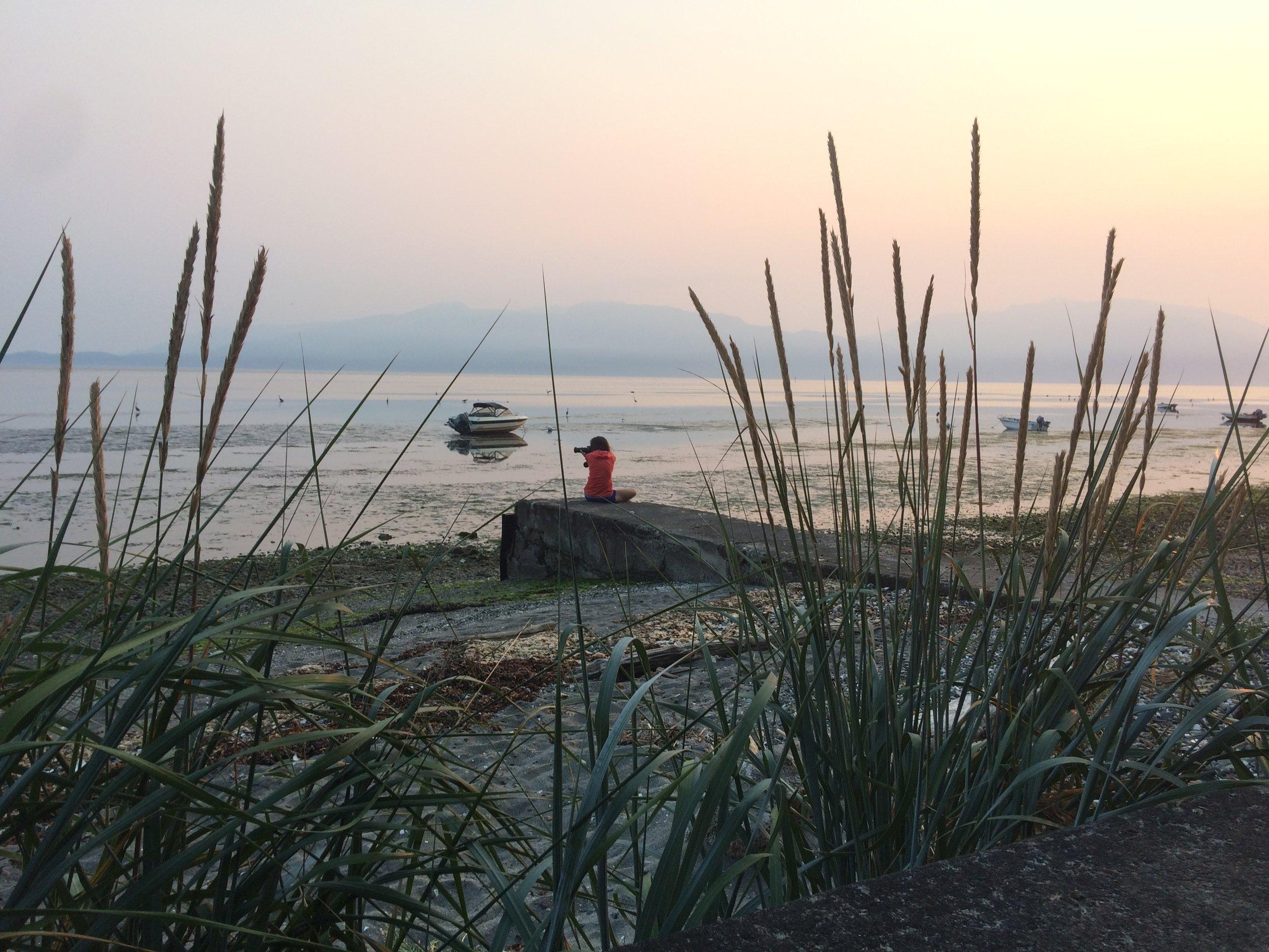 Cara at dawn taking photos of the blue herons. We staged at Samish Island.