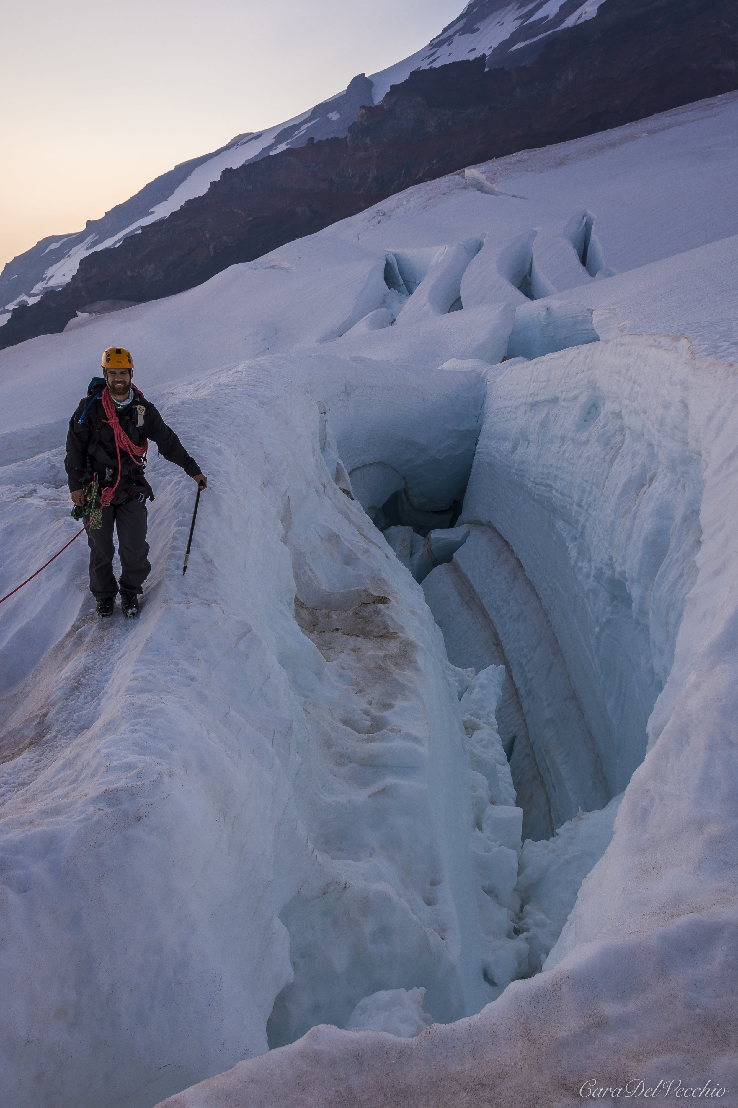 Adam beside a crevasse with more behind him. Note the striation of the glacier.