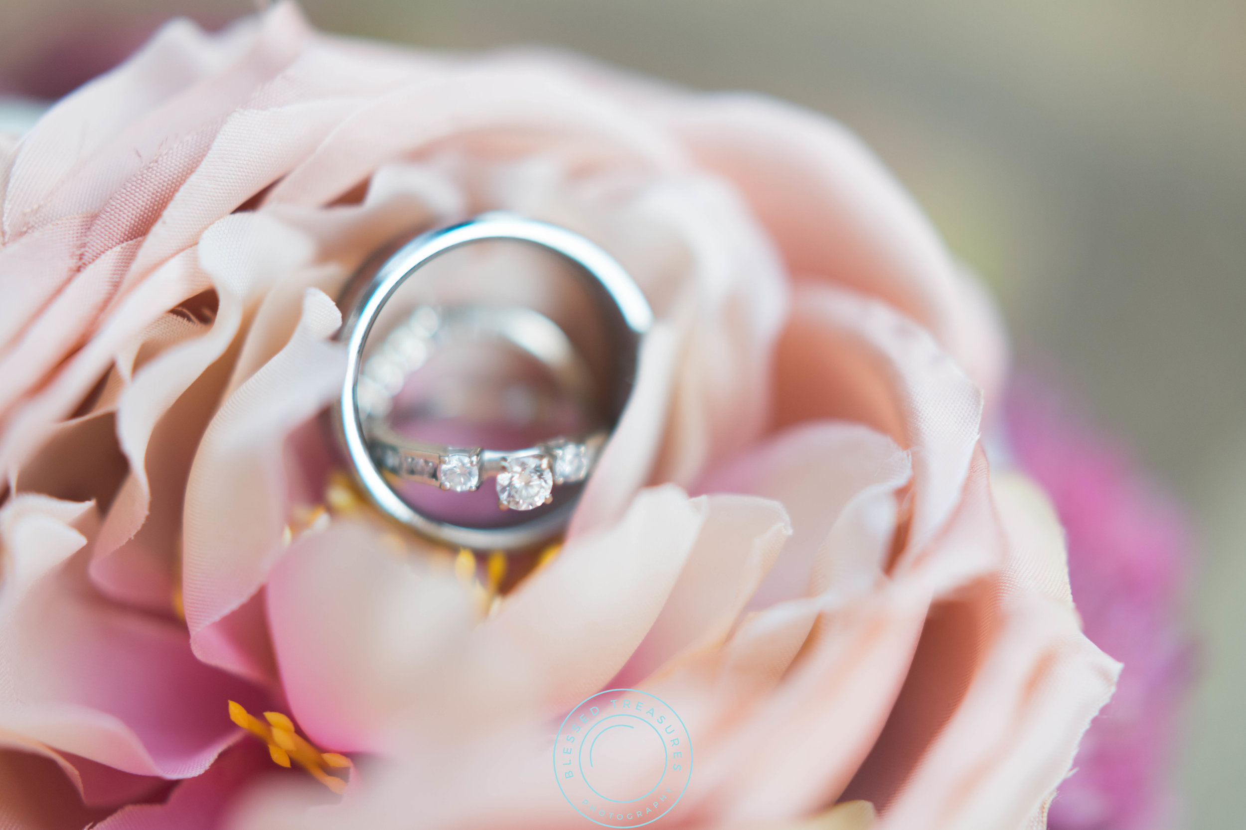 delicate diamond wedding ring wooden wedding band on pink rose flower bouquet