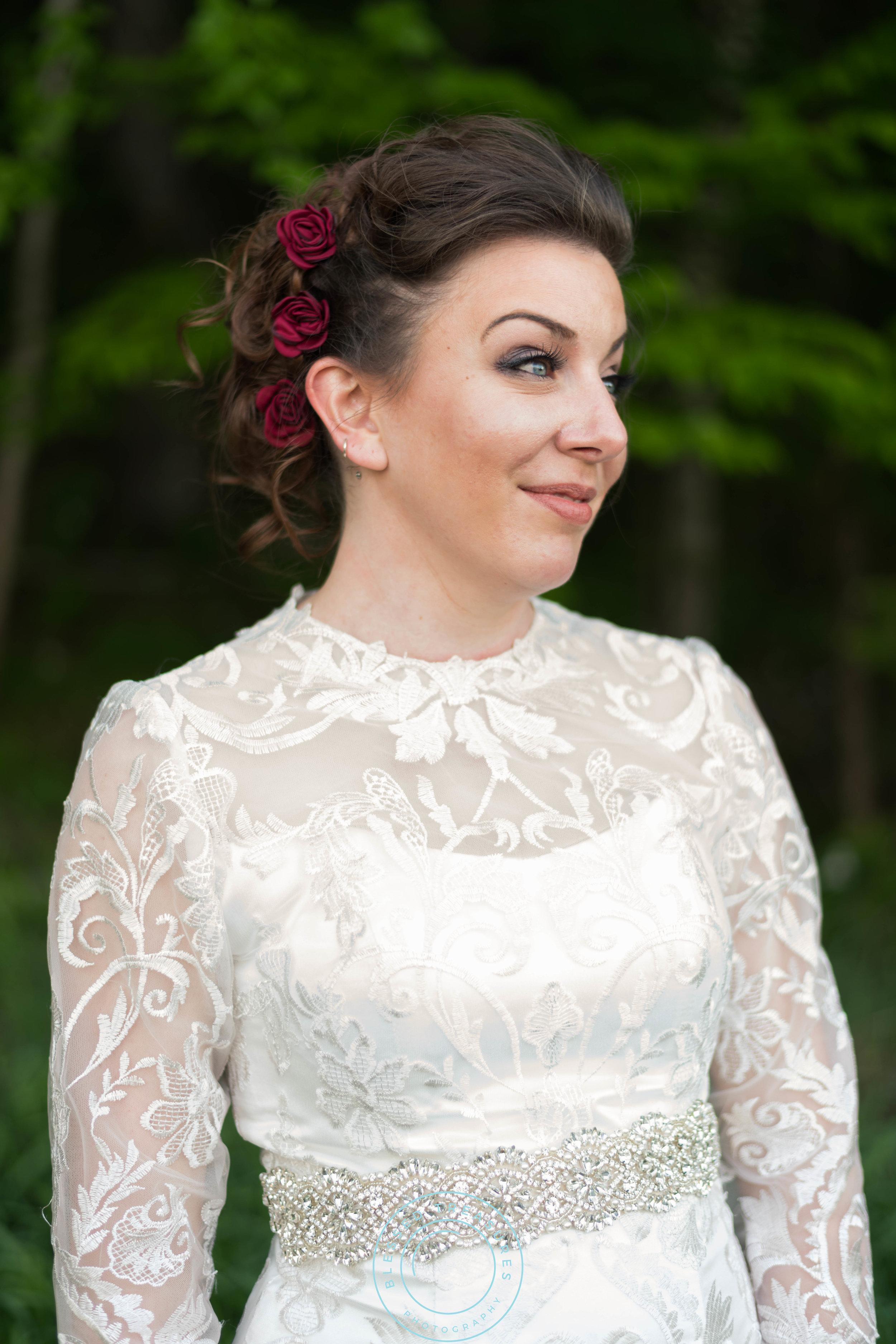 curly brunette wedding updo red roses smokey eye natural makeup lace wedding dress long sleeved beaded sash