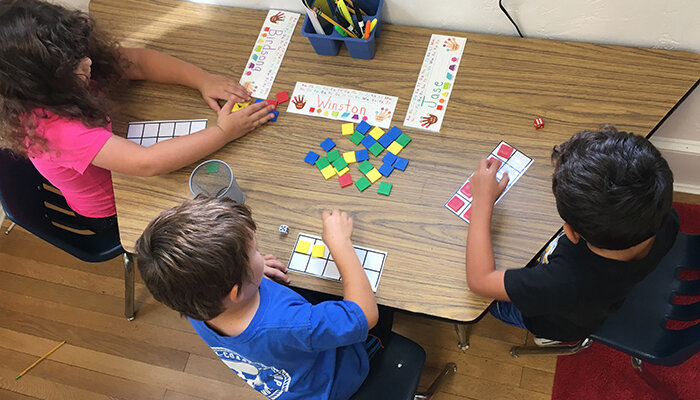 Kindergarten students work with math manipulatives.