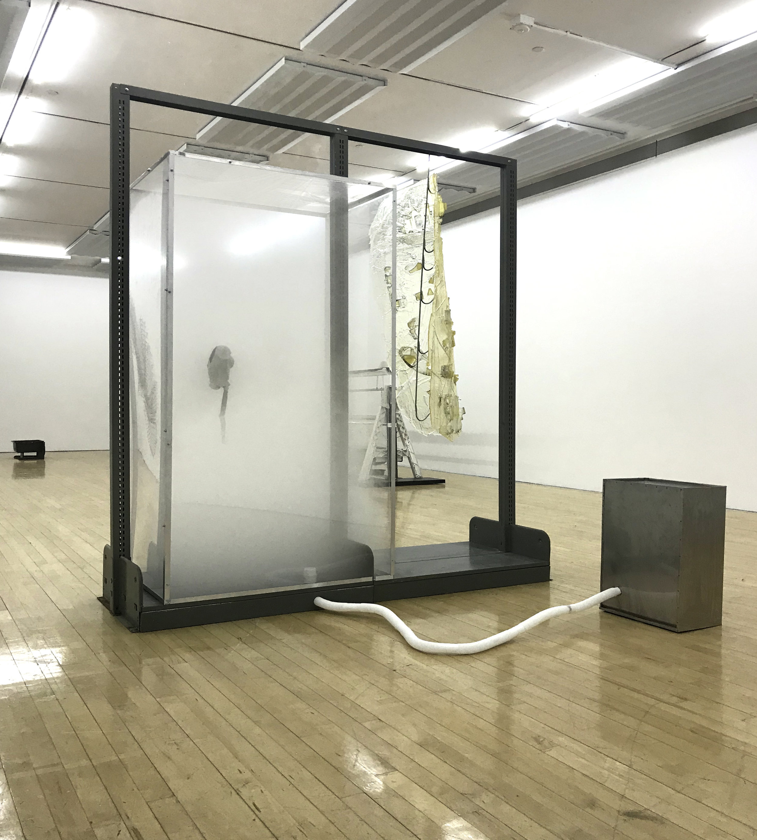 Vladislav Markov  Untitled , 2018 library shelves, Plexiglas, polyurethane engine cast, gas mask, fog machine,  plastic hose, self-adhesive carpet protector film 84 x 84 x 24 inches (213 x 213 x 61 cm) (VM3)