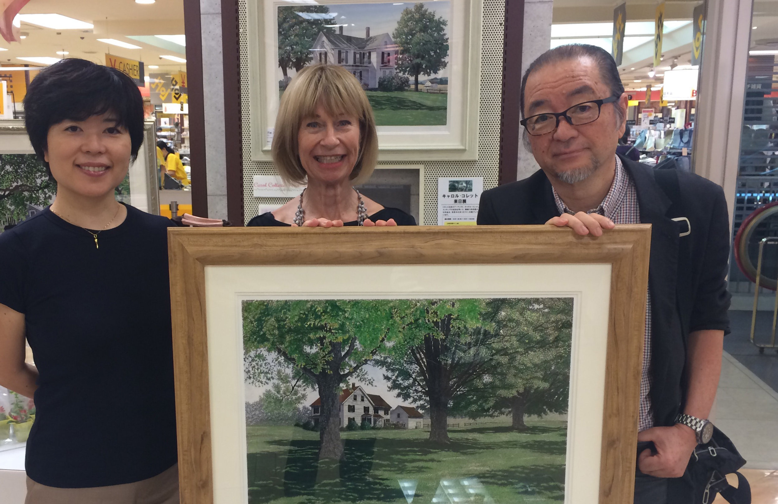 A picture of two Japanese clients and me holding one of my artworks.