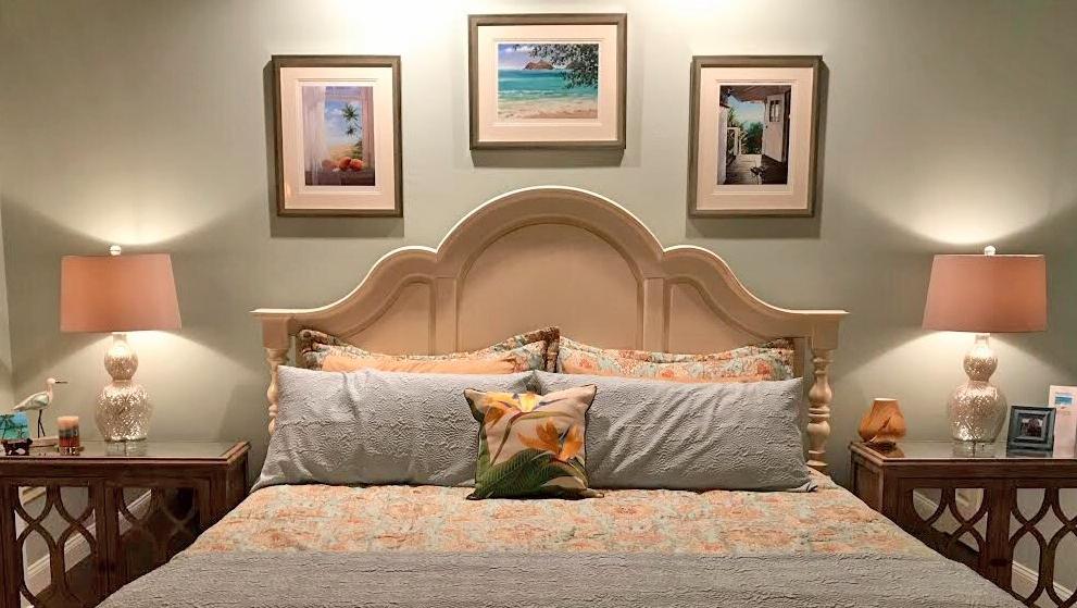 three of my hawaiian giclees adorning the wall above a bed.