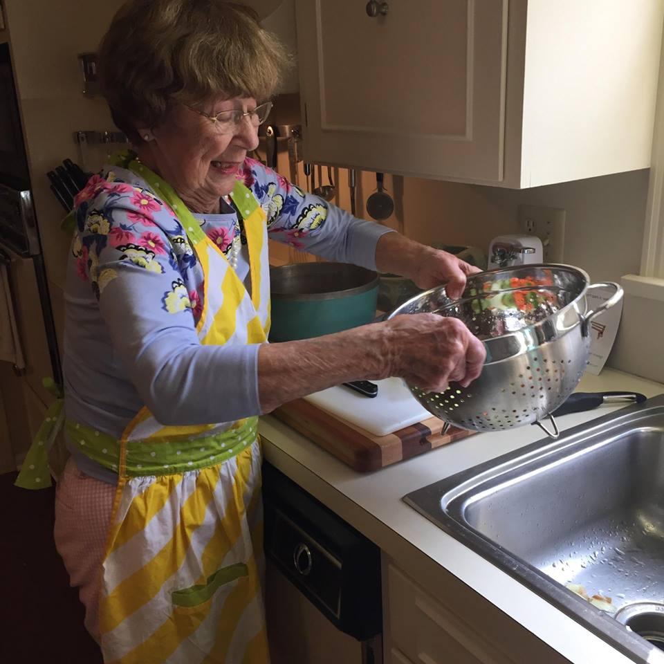 lynchburg va senior home health care - senior client cooking in kitchen with collander - companion home care inc.jpg