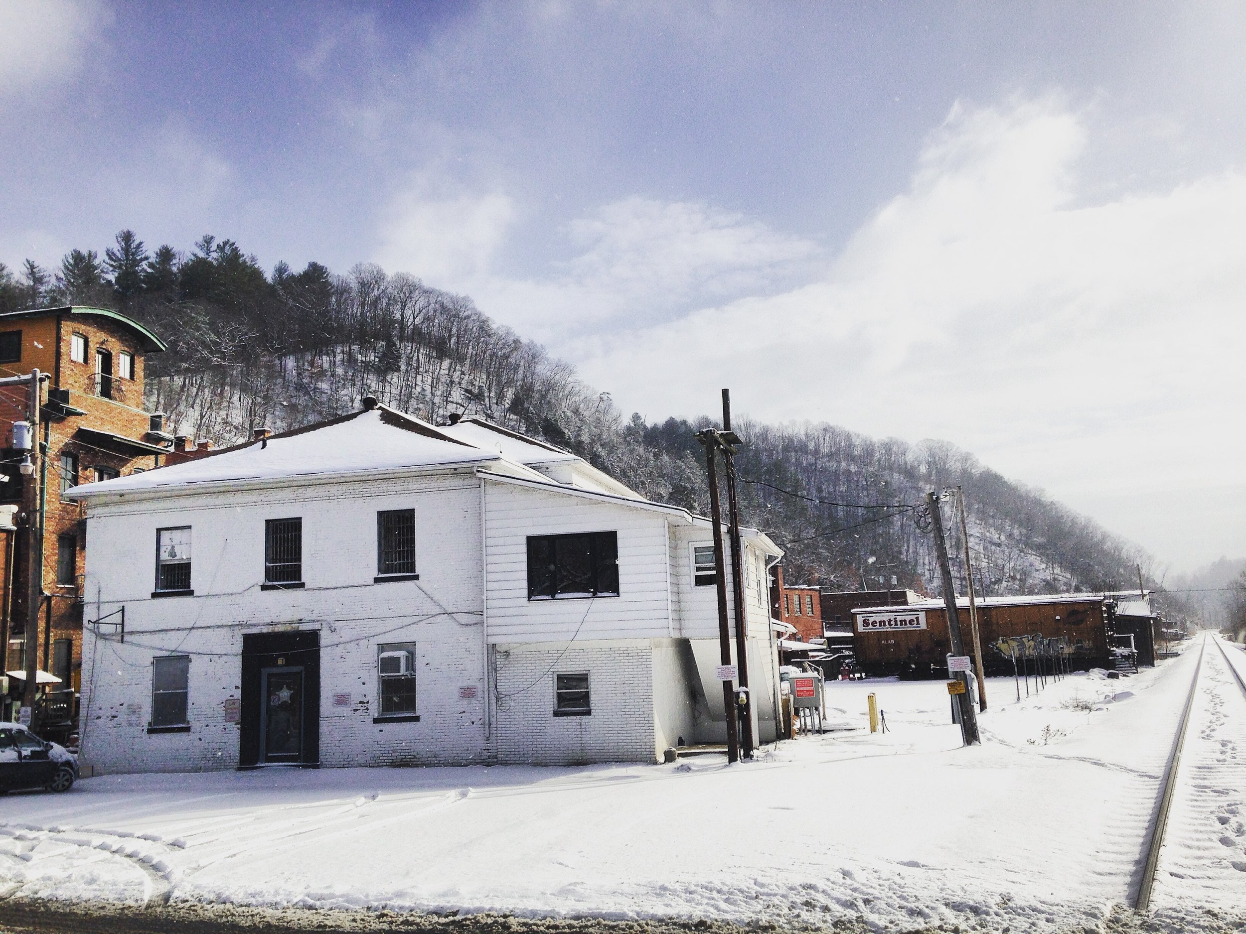 The former jail, started in 1903 and completed in 1905, sits in the center of historic Marshall beside the railroad tracks and the French Broad River.