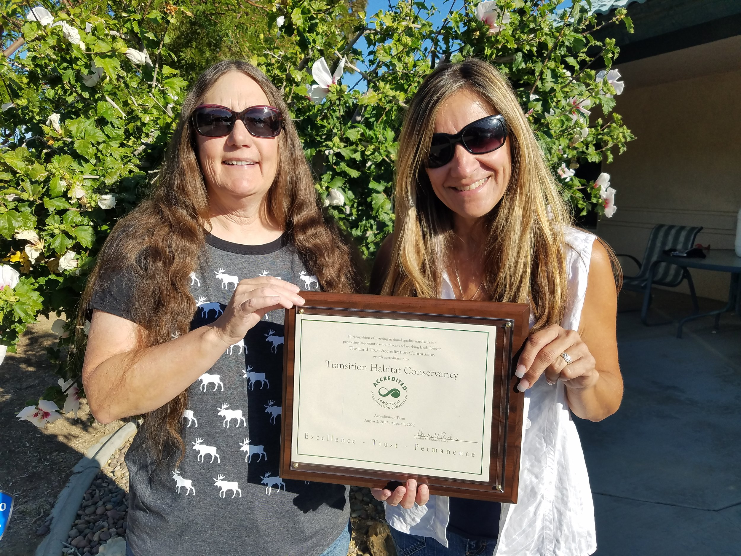 Founding Board Members, Jill Bays and Carol Hill, proudly display the accreditation certificate.
