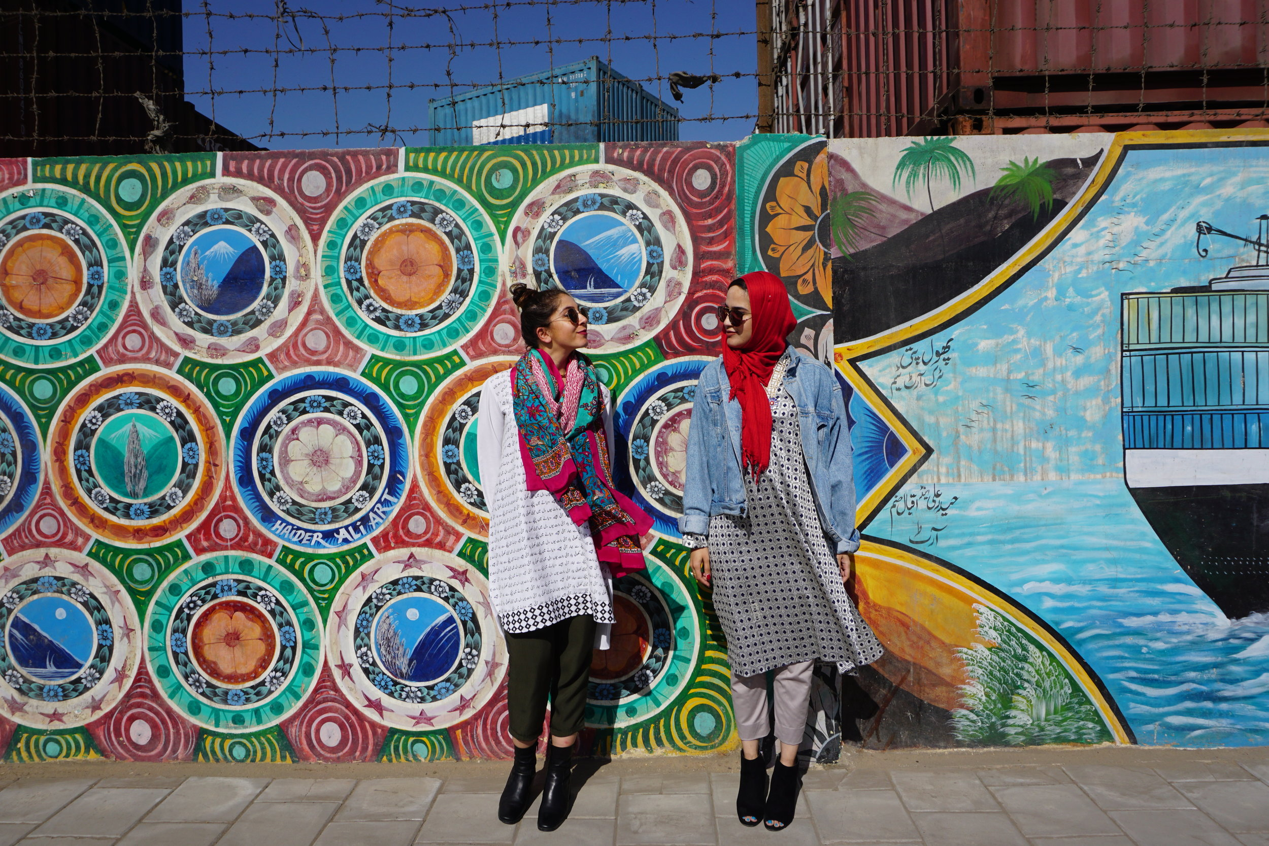 Sunya (left) and Kifah (right) stand in front of one of their favorite art series in Karachi, Pakistan