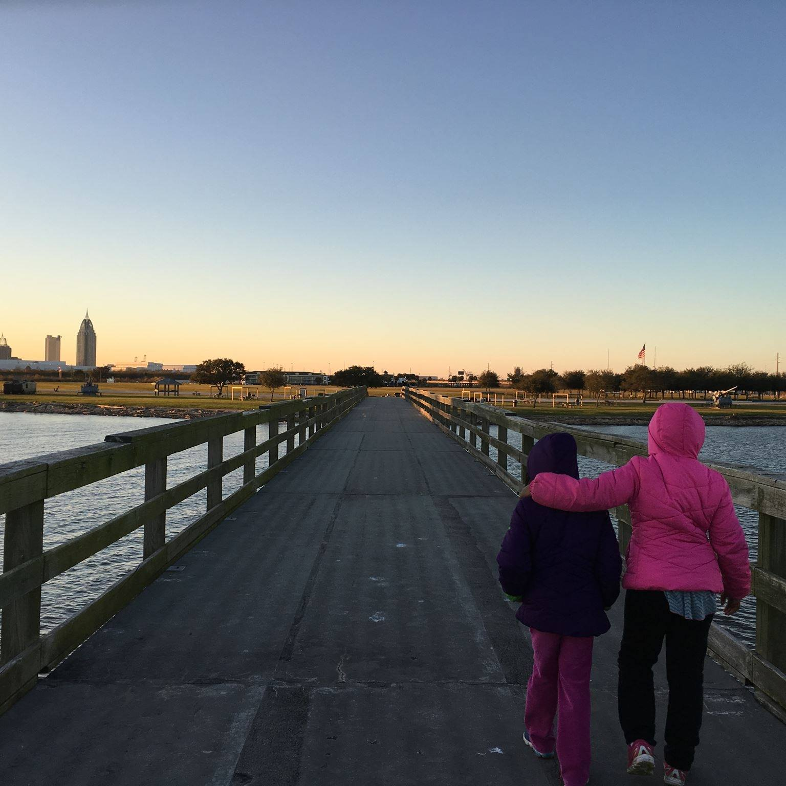 Precious's two little girls walking on a pier in Mobile Bay, in Alabama,during one of her history detective trips. They, along with her husband, have accompanied her on several of these research journeys.