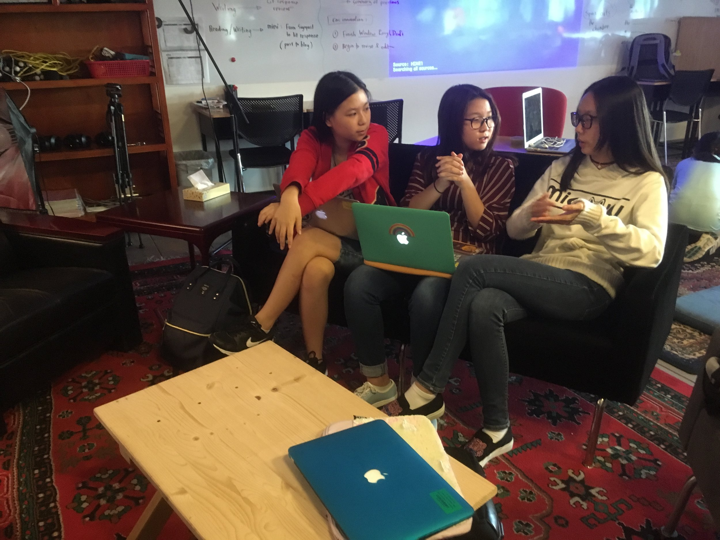 High School reporters and producers Judy P, Sally K, and Lilian H discuss their new project in the FPR workshop space.
