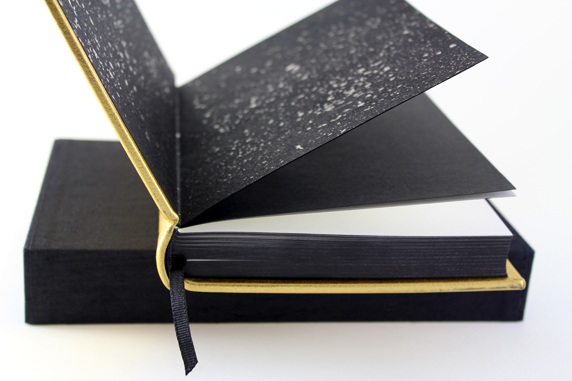 A glimpse of the handmade Cave endpapers and blackened edges on the fine edition