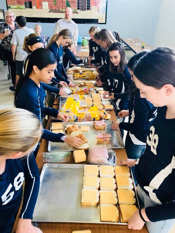 St. Timothy student-athletes work together with members of the St. Vincent dePaul society to make sandwiches for families at St. Lawrence Haven.