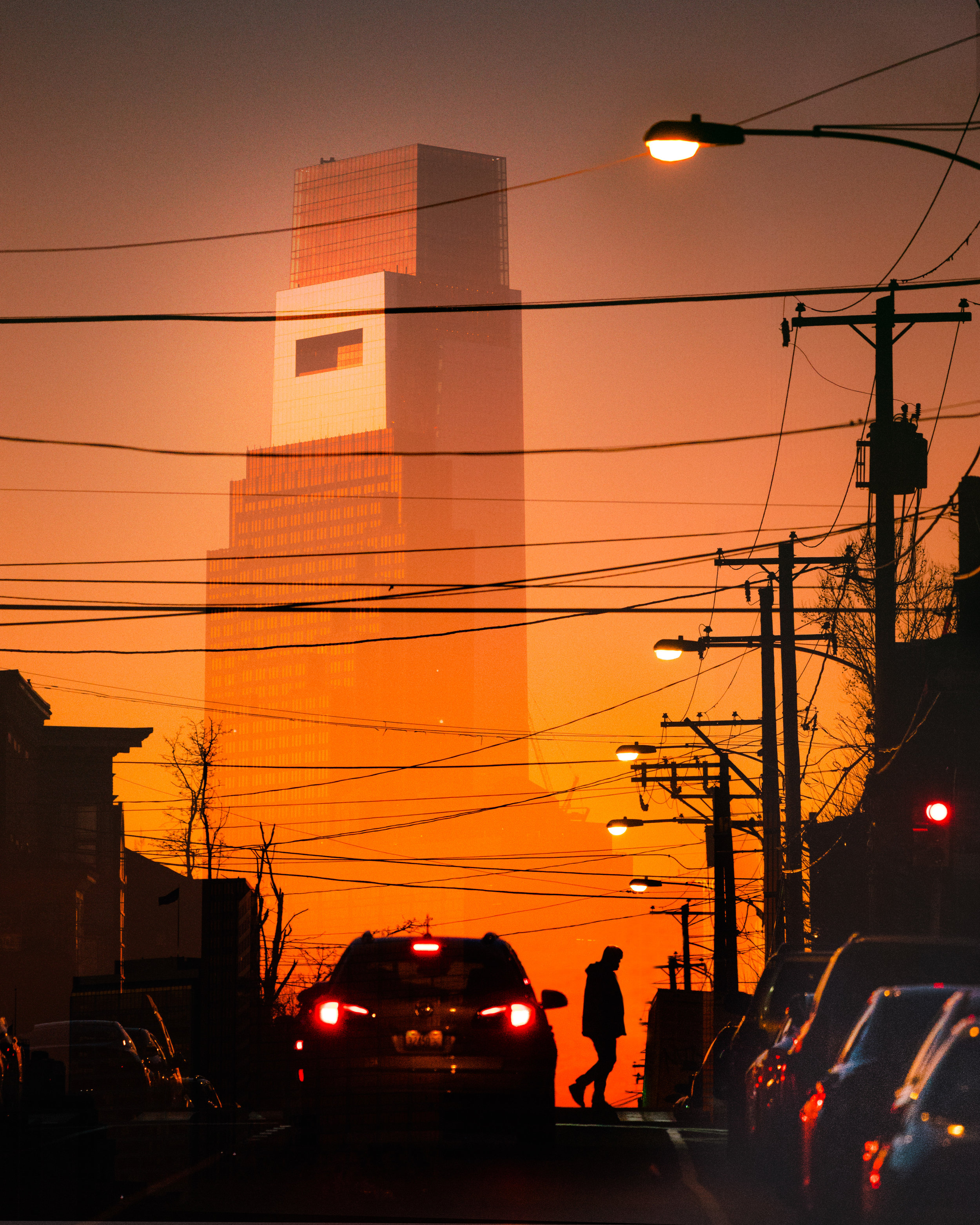 Guy Walking west philly comcast one in background sunset.jpg