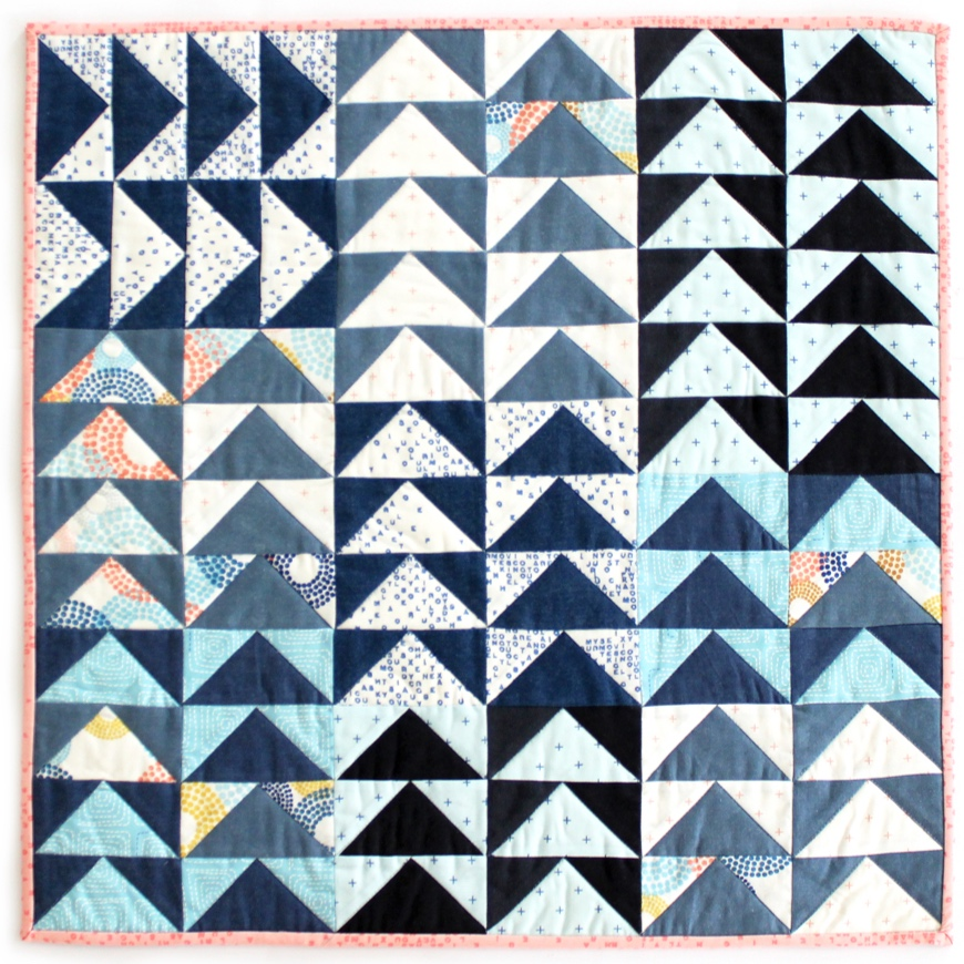 The various blue tones, crisp white, and accents of mustard, turquoise and pale pink in Breeze by Zen Chic come together for a fresh airy feel in this mini quilt. Find a free pattern for the quilt at Purl Soho.