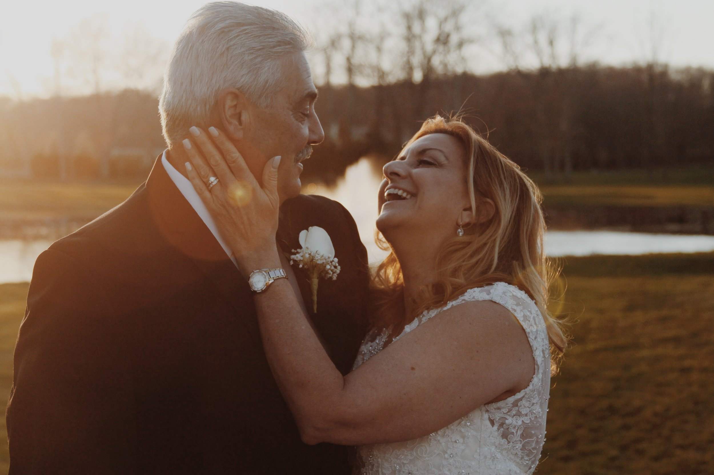 Newly married couple laughing by a lake