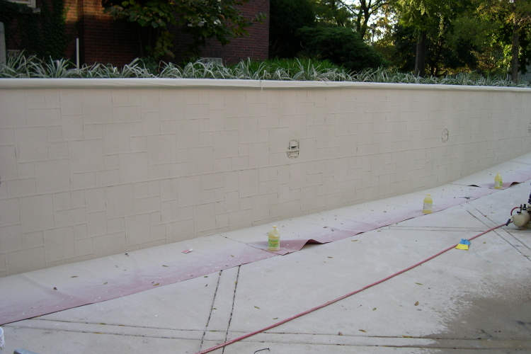 Concrete Driveway Retaining Wall Showing Cement Overlay Sprayed Over Stencil Design Template