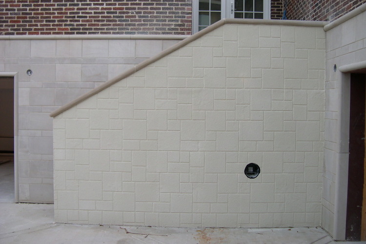 This concrete retaining wall stairway was sprayed with a thin cement overlay, using a limestone block stencil for patterning, to blend with the limestone block foundation of the home.